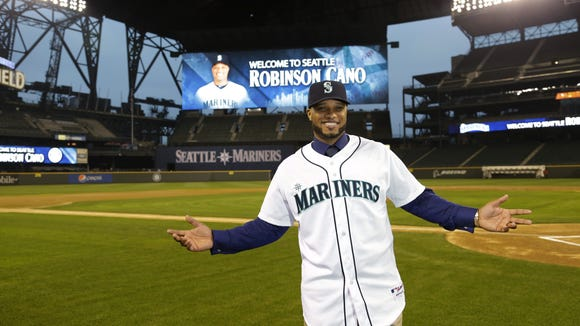 Robinson Cano poses for a photo in his new jersey at Safeco Field after he was introduced as the newest member of the Seattle Mariners baseball team Thursday.