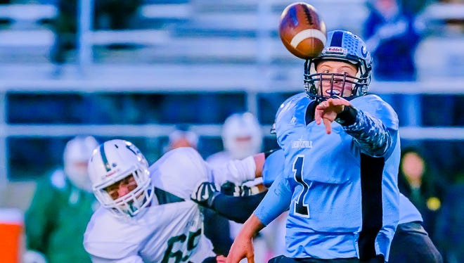 Lansing Catholic quarterback Tony Poljan tosses the ball to a teammate on an option play during the Cougars' game with Gabriel Richard.