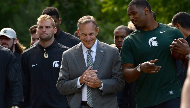 Head coach Mark Dantonio smiles as he talks with former player and honorary captain Damion Knox as they lead the team on their walk to Spartan Stadium before Michigan State kicks off football season against Furman Friday, Sept. 2, 2016 in East Lansing.