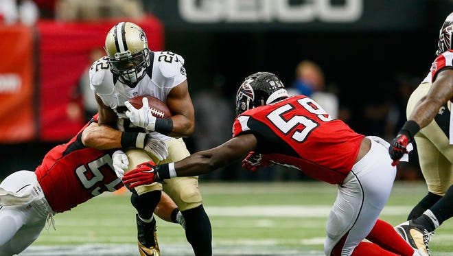 New Orleans Saints running back Mark Ingram (22) avoids a tackle from Atlanta Falcons' Paul Worrilow (left) and Joplo Bartu in the Georgia Dome on Sunday in the Falcons' 37-34 win in overtime. Ingram had 13 carries for 60 yards and two touchdowns.