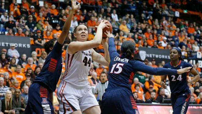 Oregon State's Ruth Hamblin, center, goes to the basket while guarded by Arizona's Breanna Workman, left, and Keyahndra Cannon in the second half of an NCAA college basketball game in Corvallis, Ore., on Friday, Jan. 29, 2016. Oregon State won 71-43.