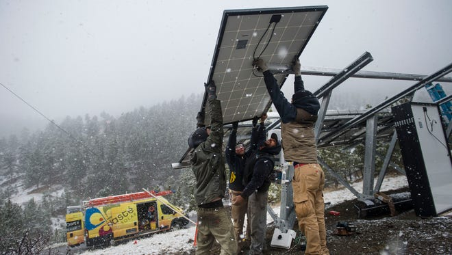 NamastŽe Solar installers, from left, Houston Sherer, Alyssa Soares, Jason Ortiz and Davis Fogerty hoist a module onto the framework of a ground mount solar panel system during an install on Wednesday, March 28, 2018, in Bellvue, Colo.