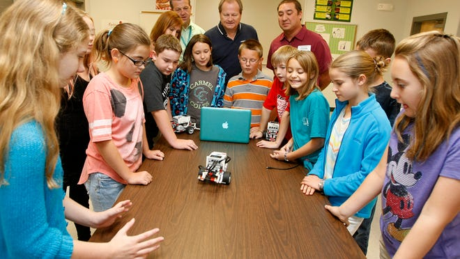 Carmel Elementary School club members demonstrate their robot to Robert Perrin, right, and Kirk Steer of Hendrickson International Monday. The pair delivered a check and donated $500 to the club.