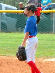 Just because she's on the ballfield doesn't mean she can't wear a big red bow.