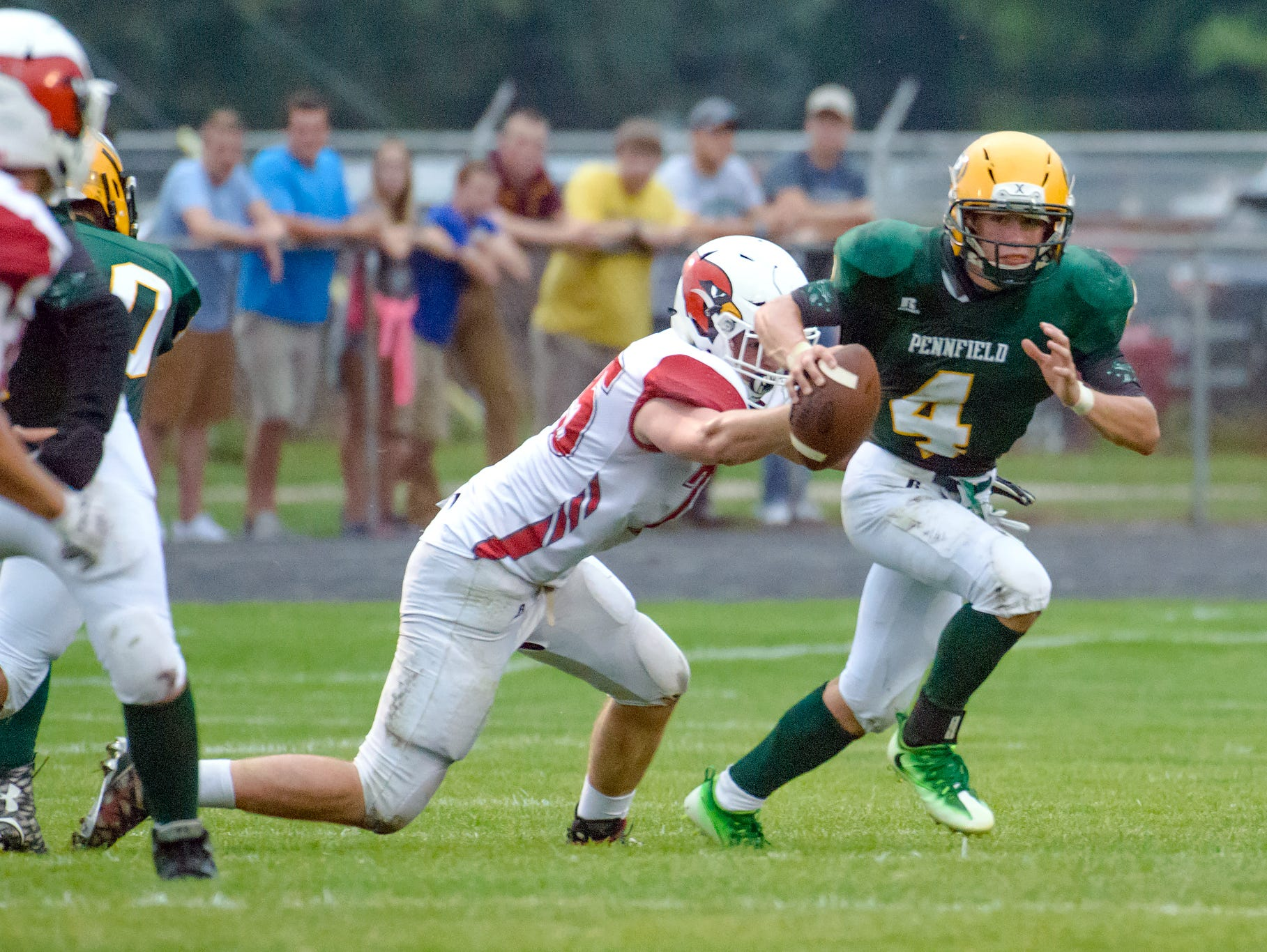 Pennfield quarterback Kollin Kemerling scrambles away from a Cardinal defender during first quarter of play Friday night.