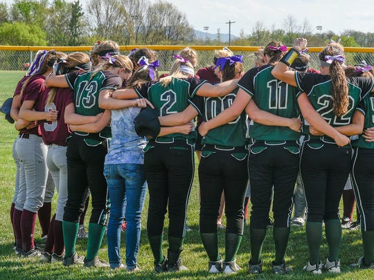 James Buchanan and Shippensburg's softball team gather together to say a prayer for Violet Clark before their softball game Tuesday, April 26, 2016.  Both teams wore wore violet ribbons in their hair and gloves in honor Clark.