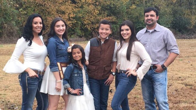 Marlon Martinez and members of his family pose for a portrait in this picture taken before his arrest last month.   From left to right: His wife Olaya Martinez, 37, children Sory, 13, Lily, 7, Marlon Jr., 11, Ory, 16, and their father Marlon Martinez, 36.