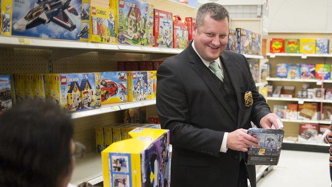 West York Borough Police Chief Justin Seibel, center, talks with Tina Trimmer, of West York, while her 4-year-old grandson, Izayah Bowie, looks for his next toy. Children shop with local law enforcement officers at Target in West Manchester Township while participating in the Shop with a Cop program, Tuesday, December 8, 2015.
