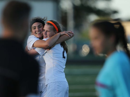 Centennial's Elizabeth Johnson and McKenzie Geiger hug each other after winning the 3A girls' soccer regional final between Ankeny Centennial and Dowling Catholic on Monday, June 6, 2016, in Ankeny.