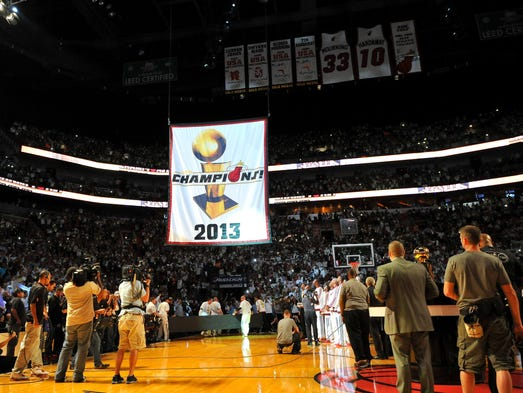 The Miami Heat's 2013 NBA championship banner is raised during a ceremony prior to the Heat's game against the Chicago Bulls.