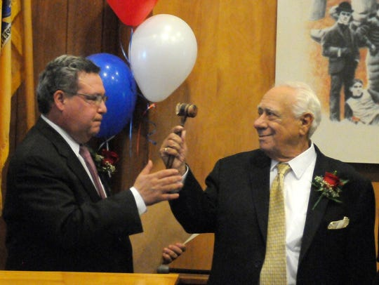 Former Nutley Mayor Peter Scarpelli, right, hands the gavel to his son, newly sworn Mayor Joseph Scarpelli, on May 17, 2016. They are the first father and son to both serve as Nutley mayor. They also both served as public works commissioner.