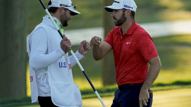 Matthew Wolff, right, bumps fists with his caddie after finishing the third round on Saturday in Mamaroneck, N.Y.