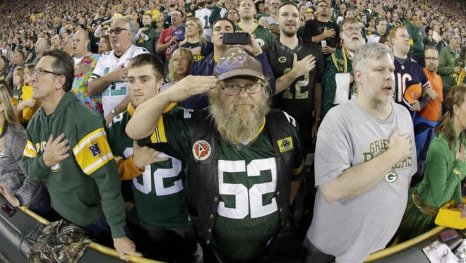 Spectators stand for the national anthem before the Green Bay Packers game against the Chicago Bears  on Thursday.