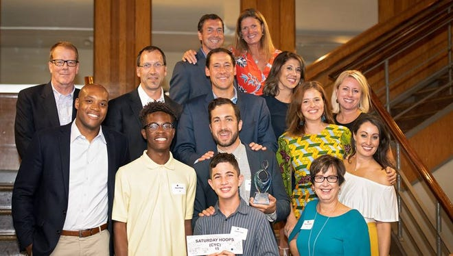 Adam Turer, middle, of Anderson Township is surrounded by friends and family after receiving the Greater Cincinnati Foundation's 2018 Emerging Philanthropist Award.