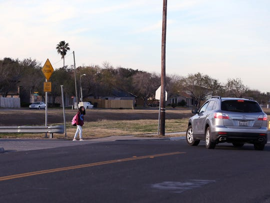 A Grant Middle School student waits to cross Aaron