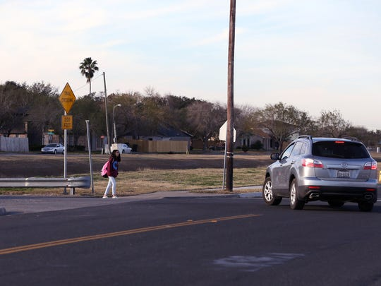 A Grant Middle School student waits to cross Aaron Drive on January 23, 2018. When the Corpus Christi Independent School District instituted later end times this year, the city, along with the district, decided not to change school zone signage due to the cost of replacing the signs, the intention of CCISD in seeking a District of Innovation status and the time it would have taken to replace and reprogram the nearly 1,000 plaques and 149 flashing signs before school started.
