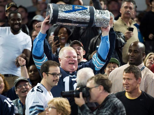 Toronto Mayor Rob Ford holds up a replica Grey Cup as he attends the Toronto Argonauts and Hamilton Tiger-Cats CFL Eastern Conference final football game in Toronto on Sunday.