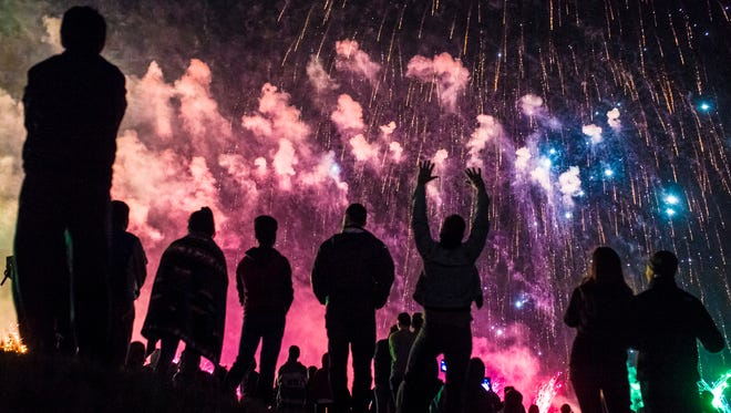 Spectators look on during the fireworks of the Thunder over Louisville event Saturday evening. The day was mostly gray with scattered showers, but cleared in the late evening as more spectators arrived. April 22, 2017