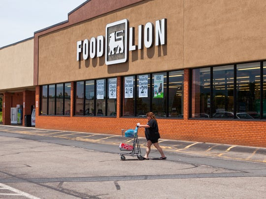"""Robin Fitzgerald walks a cart through Food Lion's parking lot after shopping at the store in Stuarts Draft on Wednesday, June 24, 2015. """"I prefer Food Lion over Martin's,"""" Fitzgerald said after hearing of the recent merger between the stores' parent companies. """"More for your money."""""""
