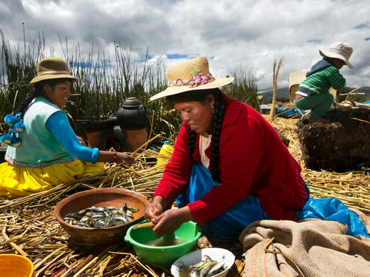 From left, Danesa Mamani Suana and Margarita Aruquipa Apaza prepare a meal of freshly caught killifish on a floating reed island in Lake Titicaca in Peru. About 2,000 Uros people live on floating islands in the middle of what is the largest lake in South America.