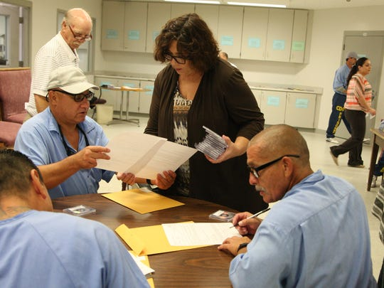 Volunteer  Willie Horenburg helps inmates get ready to complete their recordings with The Messages Project.