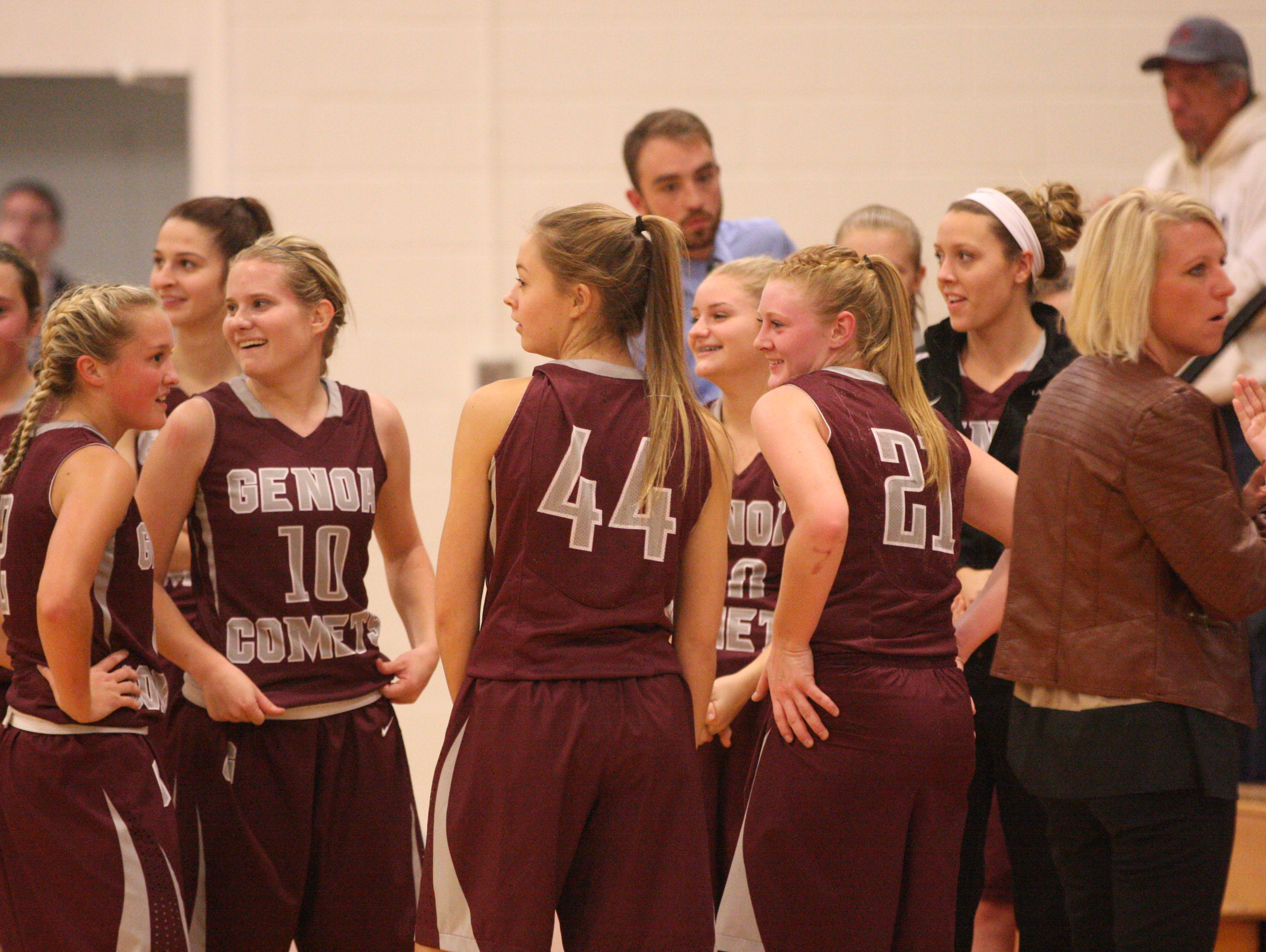 Genoa's Haley Pickard (21) smiles along with teammates as Comets fans unveil signs denoting Pickard's 1,000th career point.