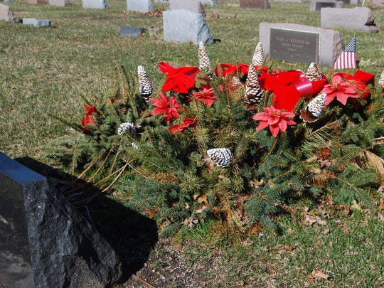 a grave blanket covers a grave at lakeside cemetery - Christmas Grave Decorations