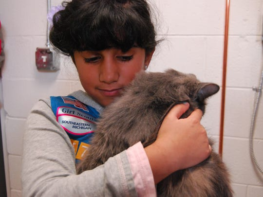 Amaya Graebert, 8, of China Township cuddles with female cat named Sandy at the St. Clair County Animal Control Shelter.
