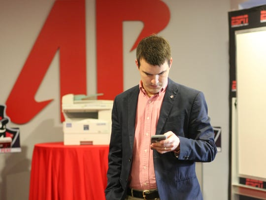 Austin Peay coach Will Healy checks his phone in-between