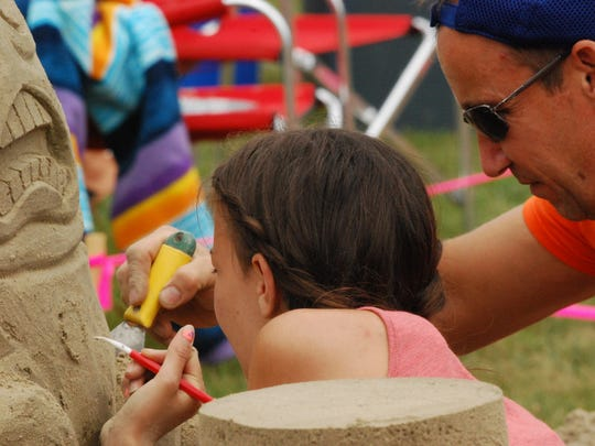 Tony and Alessia Palumbo, of Stoney Creek, Ontario, work on a sculpture depicting Humpty Dumpty, Garfield and Odie.