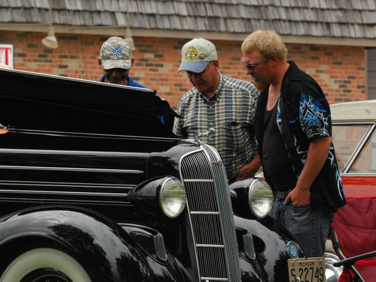 Gary Minnie, center, talks about his 1936 Dodge convertible