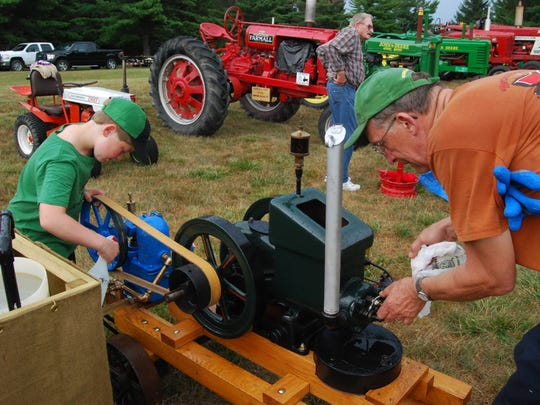 Joe Kaidan, left, helps his grandfather, Larry Osborn, with a one-cylinder gasoline engine Friday at Grant Township Heritage Day.