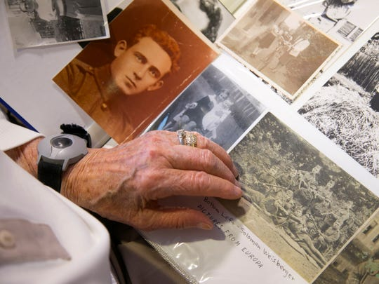 Magda Willinger, a Holocaust survivor, looks at photos