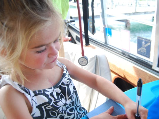 Mia Wilson, 5, writes on a notepad. She and her family are traveling by boat around the eastern United States.