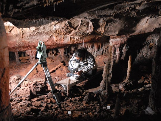 A researcher works in the cave where a lion pelt was