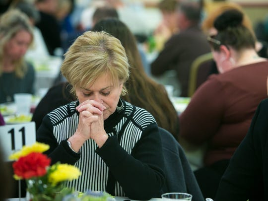 Carol Dehorty of Wilmington joins in the moment of prayer as guests enjoy a Spanish dinner hosted by the Emmanuel Dining Room where all proceeds help the Emmanuel Dining Room feed those in need every day.