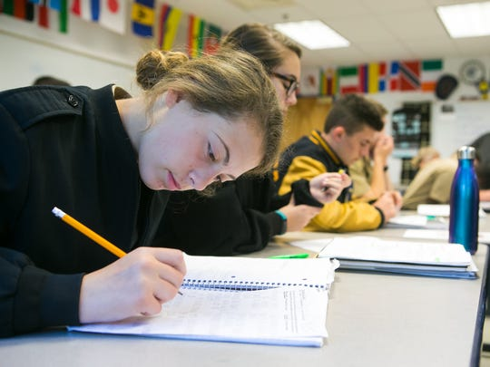 Emily McKenna takes notes in Greg Caskey's economics class at Delaware Military Academy, as they discuss the pros and cons of minimum wage after listening to his rap song 'Debatin' the Wage'.