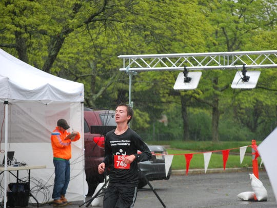 Timothy O'Sullivan, 16, of Bridgewater, crosses the finish line first at the Freedom House 5K Run & Walk on May 13.