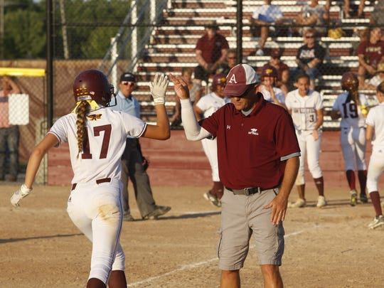 Ankeny's Malea Daugherty receives a high-five from coach Dave Bingham after hitting a grand slam in 2017. She'll return next year for her junior season.
