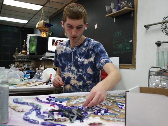 Eli Gaccione, 17, of Johnson City, works on a mosaic