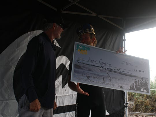 A check is presented to surfer Aaron Cormican from Jeff Kugel for the King of the Peak surf contest Nov. 5 in Sebastian Inlet.