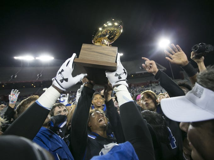Chandler players celebrate with the championship trophy
