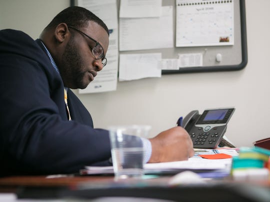 State Secretary of Labor Cerron Cade works in his office at Wilmington's Department of Labor.