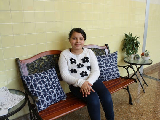 Third-grader Jada Morales, 9, sits on the reflective bench at Horace Mann Elementary School to think and write.