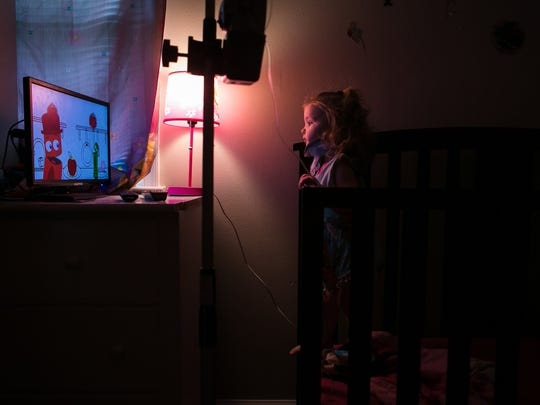 Ashlyn Rea, 2, watches a show on television from her crib as she's hooked up to an IV for her weekly enzyme replacement therapy. Ashlyn and her sister Ember, 3, along with her brother, Christopher, 18, all have Morquio syndrome, a rare condition that one in 250,000 people have.