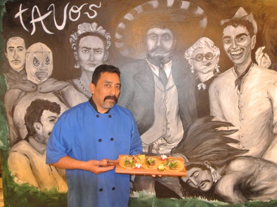 Gustavo Camacho, standing at a mural in his new restaurant,