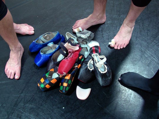 SNB male dancers' feet after a tough pointe workout, with individually designed and painted pointe shoes.