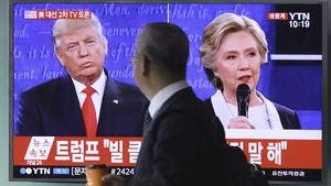 People watch a TV screen showing the live broadcast of the U.S. presidential debate between Democratic nominee Hillary Clinton and Republican nominee Donald Trump on Oct. 10 at Seoul Railway Station in Seoul, South Korea.