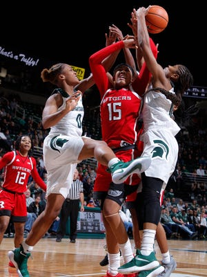 Michigan State's Shay Colley, left, Rutgers' Caitlin Jenkins, center, and Michigan State's Branndais Agee, right, battle for a rebound, Sunday, Dec. 31, 2017, in East Lansing, Mich. MSU fell 61-58.