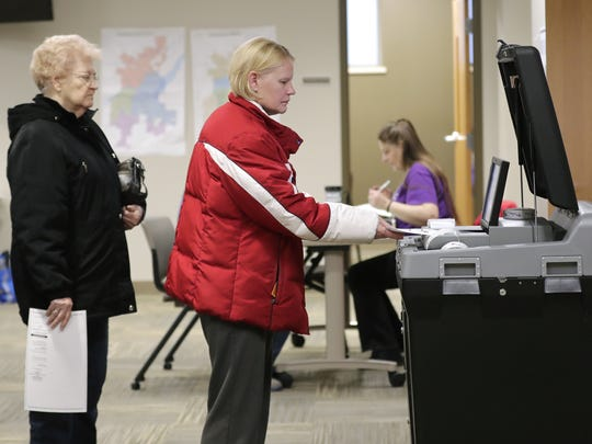 Irene Krueger, left, and Kathy Ward feed their ballots into a voting machine Tuesday at the Kaukauna Municipal Services Building.